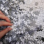 An employee of puzzle maker Beverly holds a piece of the company's white micro 1000 piece jigsaw puzzle at the International Toy Show in Tokyo June 14, 2012. REUTERS/Yuriko Nakao