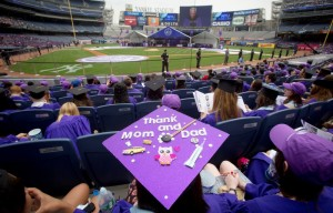 A graduate from New York University sits in the stands of Yankee Stadium, while wearing a mortarboard with a message on it, during a commencement ceremony in the Bronx borough of New York on May 21, 2014. REUTERS/Carlo Allegri